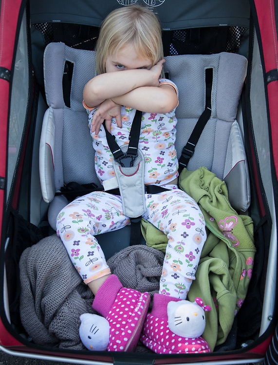 Three year old Cora, wearing her older sisters slippers, is out for a ride with her mother in Calistoga