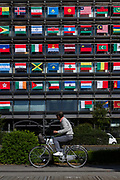A man rides a bicycle in front of the Offices of the Mainichi Newspaper Company display all 206 flags of the countries taking part in the 2020 Tokyo Olympic Games. Chiyoda, Tokyo, Japan. Friday October 27th 2017. Saturday October 28th marks 1,000 days before the opening ceremony of the Summer Olympics in Tokyo. Each flag is 210 centimeters wide and 140 centimeters high and is being draped over windows on the south side of the building, facing the Imperial Palace