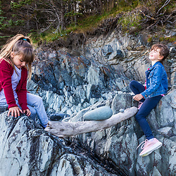 Two young girls balance rocks on a driftwood log in a cove in Quoddy Head State Park in Lubec, Maine.