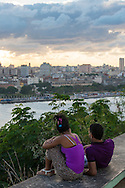 A young man and woman take in the view, looking across Havana Harbor, from a hill at the base of the Christ of Havana sculpture (Cristo de La Habana) in Havana, Cuba
