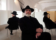 """Michelangelo Pistoletto portrait against his artistic work<br /><br />The artist (born 25 June 1933) is an Italian painter, action and object artist, and art theorist. Pistoletto is acknowledged as one of the main representatives of the Italian Arte Povera. His work mainly deals with the subject matter of reflection and the unification of art and everyday life in terms of a Gesamtkunstwerk<br /><br />In 1996, he founded the art city Cittadelarte – Fondazione Pistoletto in a discarded textile factory near Biella. Its objective, in brief, is """"to inspire and produce a responsible change in society by means of creative ideas and projects."""" Nowadays Pistoletto is particularly concerned with environmental issues, and to develop awareness about using only what we need and to create awareness about over consumption."""