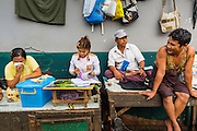 09 JUNE 2014 - YANGON, MYANMAR: A woman does her accounting at a stall in the San Pya Fish Market (also spelled Sanpya). San Pya Fish Market in Yangon is one of the largest wholesale fish markets in Yangon. The market is busiest in early in the morning, from before dawn until about 10AM.    PHOTO BY JACK KURTZ