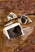 Three old CRT computer monitors are found dumped in the water in a side channel of the Middle Fork Snoqualmie River near North Bend, Washington.