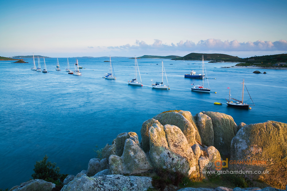 A row of moored yachts captured from Braiden Rock, Tresco. Bryher is seen to right side. Isles of Scilly, Cornwall, UK.
