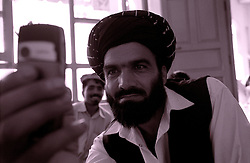 A political campaigner takes a picture with his mobile phone during an electoral meeting in Khost