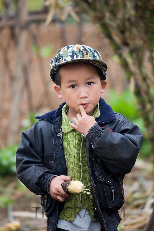 Young boy eating a piece of sugar cane near Fuli Old Town, Xingping, China