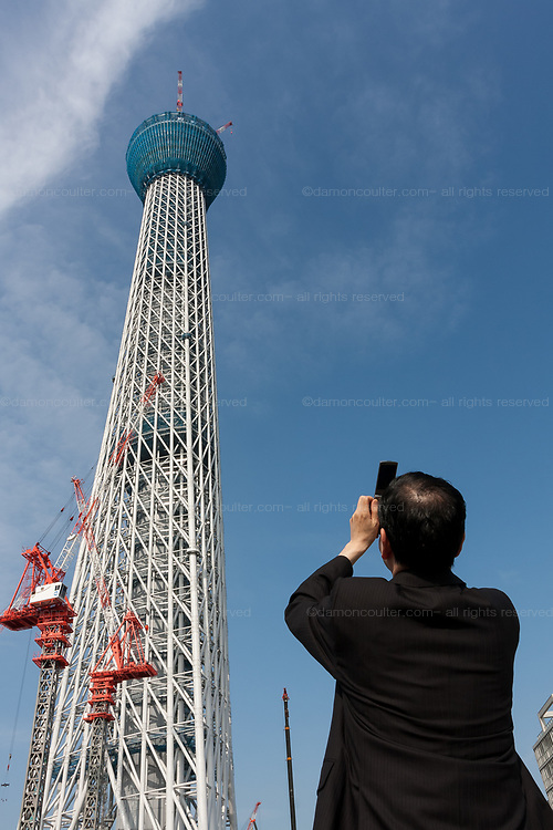 A Japanese salaryman take a photo of Tokyo Sky Tree under construction. Tokyo, Japan. Monday June 21st 2010. In this image the unfinished telecommunication tower stands at 398 metres high, Upon completion it will measure 634 metres from top to bottom, becoming the tallest structure in East Asia.