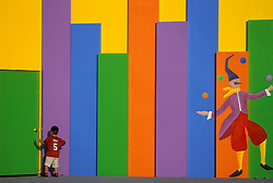 Stock photo of a young boy standing in front of a bright multi-colored decorative wall