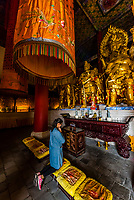 A Buddhist woman praying, Chongsheng Temple, Dali, Yunnan Province, China. The temple dates from the 9th and 10th centuries.