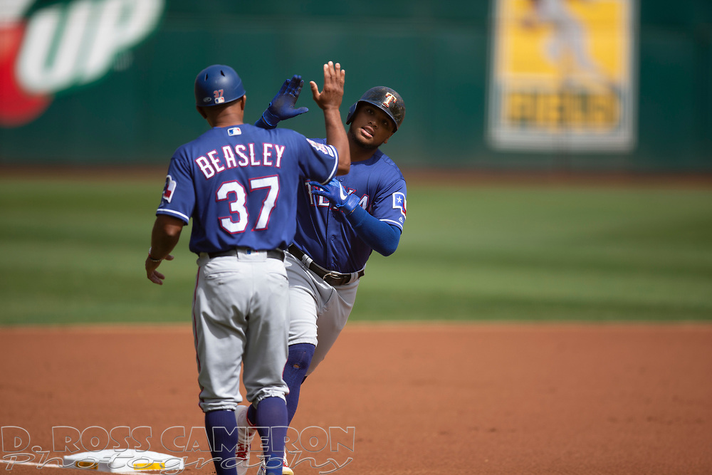 Texas Rangers' Willie Calhoun, right, gets congratulatory high five from third base coach Tony Beasley (37) after hitting a solo home run off Oakland Athletics starting pitcher Tanner Roark during the first inning of a baseball game, Sunday, Sept. 22, 2019, in Oakland, Calif. (AP Photo/D. Ross Cameron)