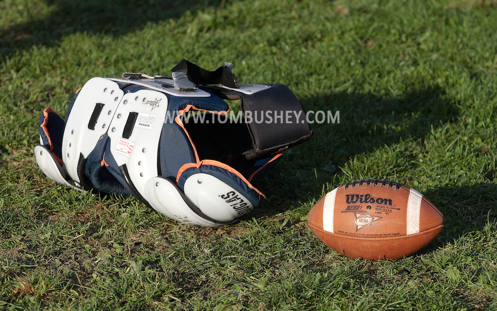 Beacon, New York - Shoulder pads and a football on the grass at a  high school football game on Saturday, Oct. 10, 2009.