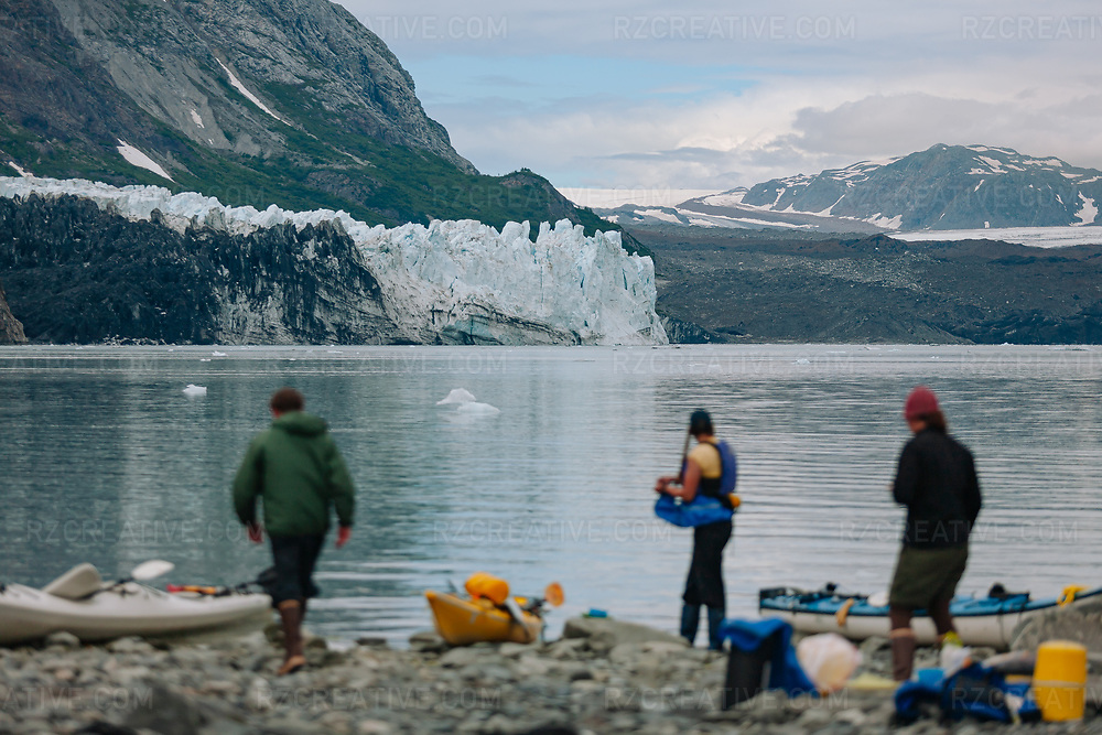 A group of paddlers stand on a beach in Tarr Inlet in Alaska's Glacier Bay National Park and Preserve. Margerie Glacier can be seen in the background. Photo © Robert Zaleski / rzcreative.com<br /> —<br /> To license this image contact: robert@rzcreative.com