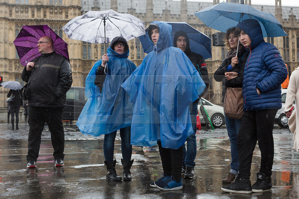 © Licensed to London News Pictures. 15/04/2016. London, UK. Tourists are caught in heavy rain showers in central London during wet and windy weather today. Photo credit : Vickie Flores/LNP