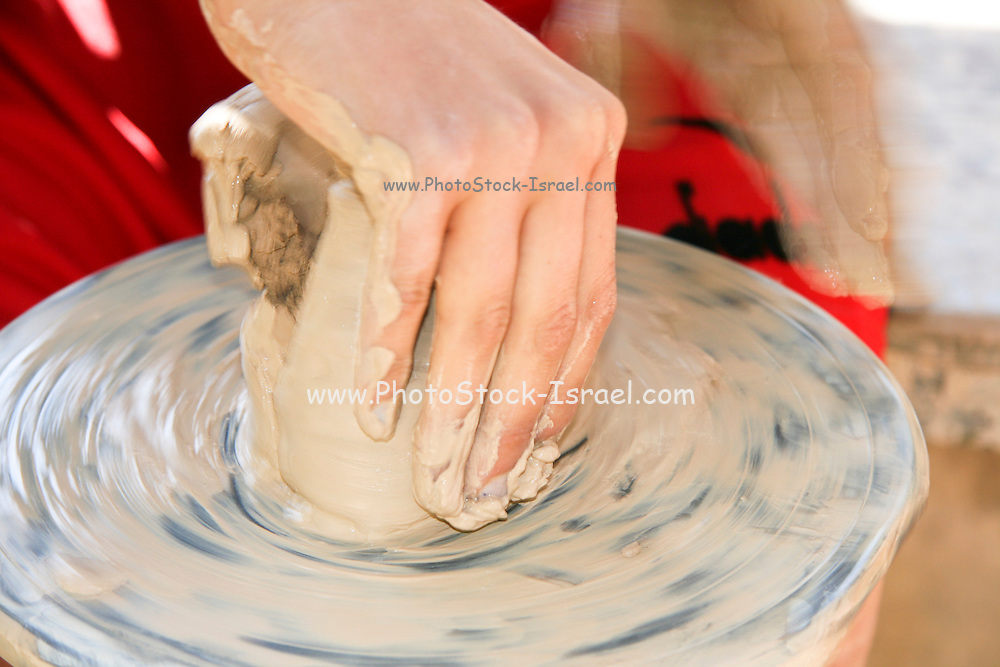 Young female teen making a clay pot on a potters wheel.