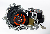 29 July 2004:  Photo Illustration of NHL ice hockey pucks locked up with chains under lock & key.  The National Hockey League and NHL Players Union are still undergoing talks of a new labor agreement.  Owners want cost certainty, players do not want a salary cap. Average salary of an NHL player is $1.8 million (US) and is taking up to 75% of the leagues revenues.  Players salaries have grown 261% since the 1995 agreement.  Current agreement is due to expire on September 15, 2004. Mandatory Credit:  Shelly Castellano/Icon SMI