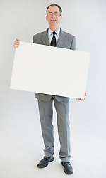 Portrait of mature man holding blank whiteboard, smiling