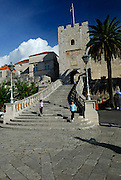 Two children (5 years old, 9 years old) on the stairway at the Revelin Tower and land gate (Kopnena Vrata) entrance into the old town of Korcula. Korcula old town, island of Korcula, Croatia.
