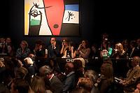 "Christie's telephone auctioneers during the 24th of June 2014 Impressionists sale. On the wall ""Femme à la voix de rossignol dans la nuit"" by Joan Miró."