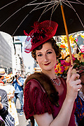 New York, NY - April 16, 2017. A woman under an umbrella, wearing a headpiece that harkens to the 1930s at New York's annual Easter Bonnet Parade and Festival on Fifth Avenue.