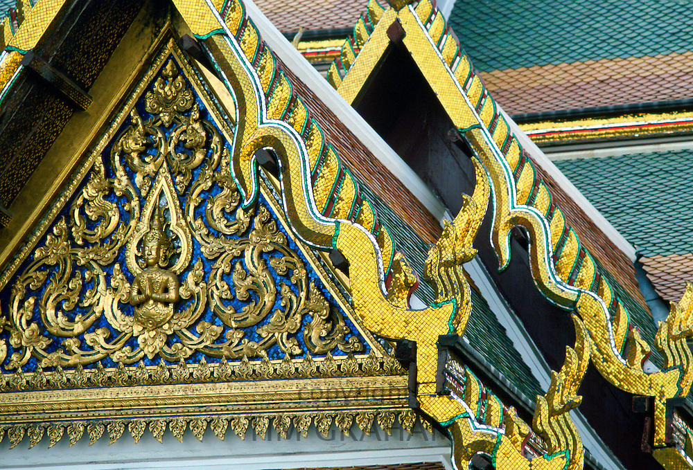 Detail of the ornate gilded woodcarving and roof tiling on the Grand Palace in Bangkok, Thailand.