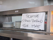 Please stand behind the mat handwritten sign in a fish and chip shop during the Coronavirus pandemic on 14th May 2020 in Knott End on Sea, Lancashire, United Kingdom.