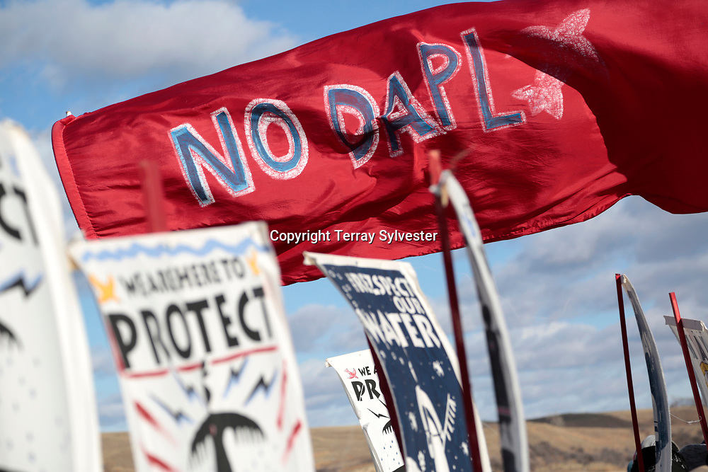 Signs and banners catch the afternoon sunlight during a rally against the Dakota Access oil pipeline on November 18, 2016. Cannon Ball, North Dakota, United States.