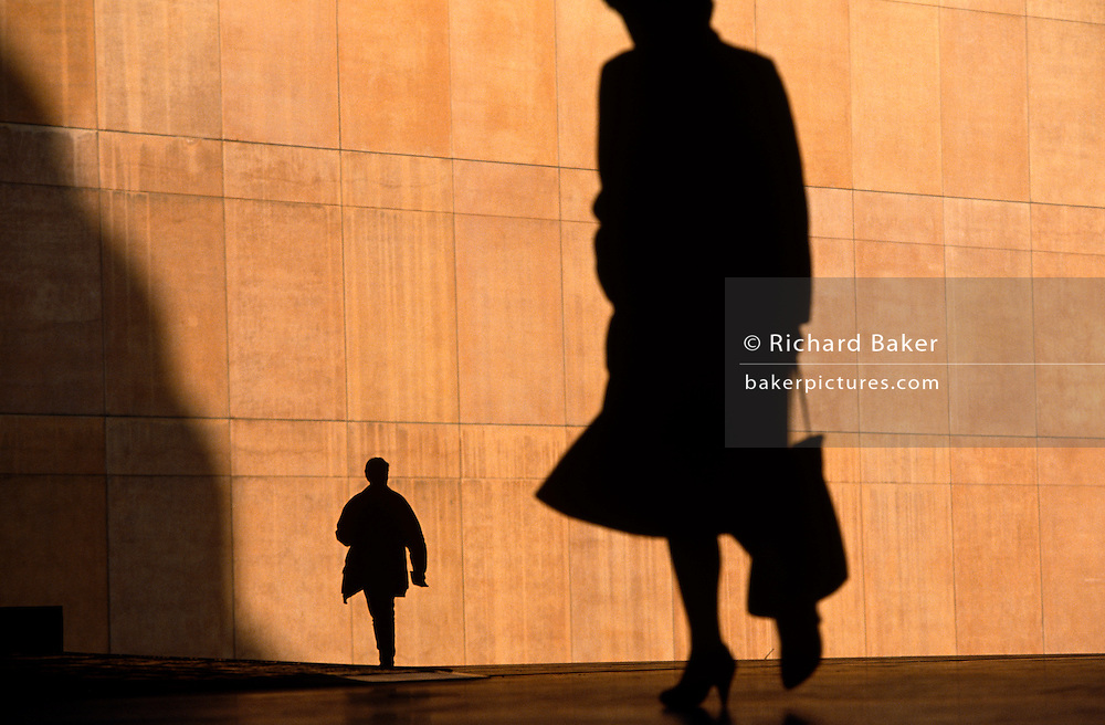 We see two office workers silhouetted against the large orange wall  of the Credit Lyonnais Bank, rushing to work through Broadgate in the City of London, UK. The figures are reduced to black shapes and without detail that may identify them or their clothes, are hurrying in different directions, one is a lady carrying a bag  but the feeling of rushing business is seen and their scale is ambiguous because  we don't know how close or far away they are from each other. The female therefore looks a  giant and the man, tiny. Broadgate Estate is a large, 32 acre (129,000 m²) office and retail estate in the City of London, owned by British Land and managed by Broadgate Estates. It was originally built by Rosehaugh and was the largest office development in London until the arrival of Canary Wharf in the early 1990s..