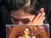 22 NOVEMBER 2016 - BANGKOK, THAILAND:  A woman wipes away a tear while singing the royal anthem to honor Bhumibol Adulyadej, the Late King of Thailand, at Sanam Luang Tuesday. Hundreds of thousands of Thais gathered across Thailand Tuesday to swear allegiance to the Chakri Dynasty in a ceremony called Ruam Phalang Haeng Kwam Phakdi (the United Force of Allegiance). At Sanam Luang, the Royal Parade Ground, and location of most of the mourning ceremonies for the late King, people paused to honor His Majesty by singing the Thai national anthem and the royal anthem.      PHOTO BY JACK KURTZ