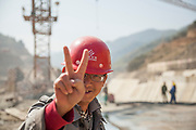 A Chinese worker with a SinoHydro helmet flashes the peace (V) sign for a photo at the construction site for Dam #5 on the Nam Ou River, Laos.