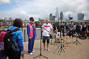 Art work by Ackroyd & Harvey made in grass with words by Ben Okri is set to float on the rising tide on the Thames on the 25th of June 2021, Central London, United Kingdom. The message is a call for action to save the planet from climate change catastrophe. Heather Ackroyd speaks at the event. The art work was moved by activists and laid onto a raft on the Thames as the tide was rising. The event marks the launch of XR Writers Rebel's Paint the Land project, which teams acclaimed writers and artists to create landscape graffitos drawing attention to the climate and ecological emergency. The Speakers at the event included the artist Ackroyd & Harvey, writer Ben Okri, Kelly Hill and Simon Bramwell, co-founder of Extinction Rebellion.  The event finished with a song by Damon Albarn and Mirabella Okra and the Capital Choir.