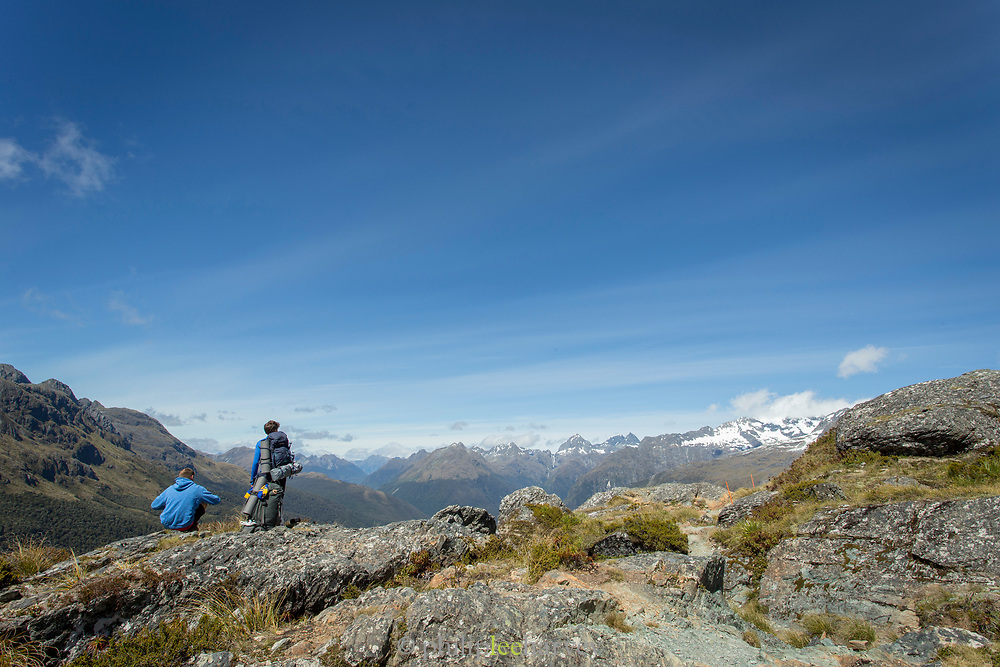 Rear view shot of two hikers looking at the view of a mountain range, Routeburn Track, South Island, New Zealand
