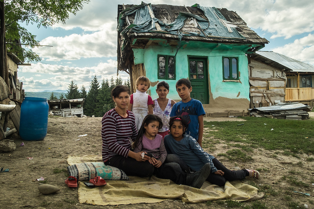 A Roma family sitting on the ground outside their home in the all-Roma village of Poiana Negustiorului in Bacau County, Romania.