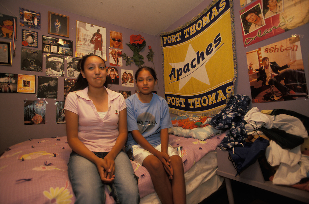 An Apache girl sits together with her sister in the sister's bedroom on the San Carlos Apache Indian Reservation in Arizona, USA.