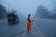 A Buddhist monk crosses busy street early in the morning, in Fang, Thailand. PHOTO TIAGO MIRANDA