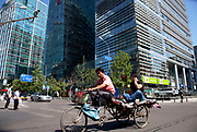 Transport workers passing the shopping malls and offices in Zhongguancun or Zhong Guan Cun, a technology hub in Haidian District, Beijing, China. It is situated in the northwestern part of Beijing city. Zhongguancun is very well known in China, and is often referred to as China's Silicon Valley. This is Beijing's computer district with numerous tech companies offices situated here amongst the many malls which sell electronics and electrons equipment of all kinds. The tech park started as a small office where two decades ago some students from a nearby university decided that computer equipment may be a thing of the future so set up a small company. It has expanded in this time to  cover many square kilometres.