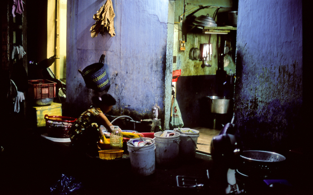 Ho Chi Minh City, Vietnam. Woman washing dishes outside restaurant.