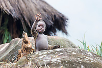 Young Mozambican child waving from near his kraal, Gorongosa Mountain, Inhambane Province, Mozambique