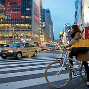 Girl on a bycicle at a busy intersection in the Shibuya district of Tokyo.