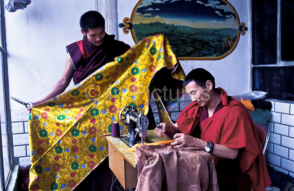 Tibetan buddhist monk Dongyu, 29  working at sewing machine with fellow monk where they are making  curtains within the complex of Atsog monastery, Xinghai County, Qinghai Province, China