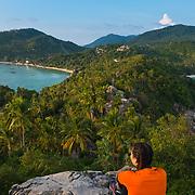 Thai girl sit on rocky cliff of John-Suwan viewpoint, Ko Tao island