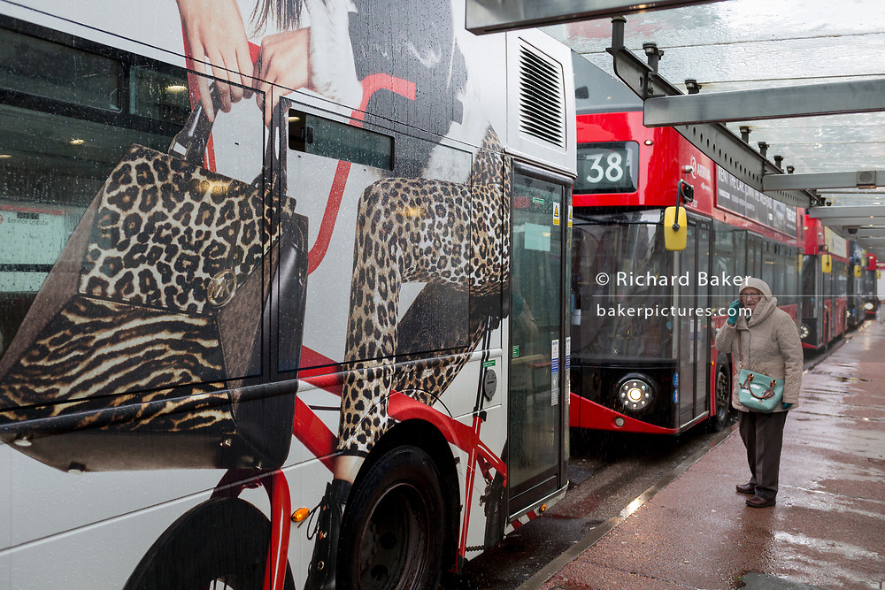 An elderly lady passenger stands in autumnal rain, next to a London bus that features an ad of style and fashion, while stopped at Victoria Station, on 17th October 2019, in London, England.