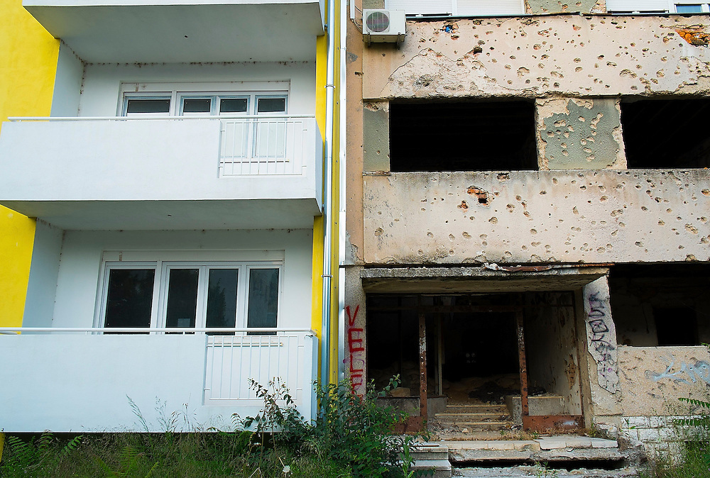 MOSTAR, BOSNIA AND HERZEGOVINA - JUNE 28: A newly refurbished building is seen next to an old derelict one from the time of 1993 war on June 28, 2013 in Mostar, Bosnia and Herzegovina. The Siege of Mostar reached its peak and more cruent time during 1993. Initially, it involved the Croatian Defence Council (HVO) and the 4th Corps of the ARBiH fighting against the Yugoslav People's Army (JNA) later Croats and Muslim Bosnian began to fight amongst each other, it ended with Bosnia and Herzegovina declaring independence from Yugoslavia. (Photo by Marco Secchi/Getty Images)