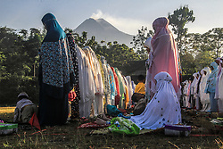 June 15, 2018 - Sleman, INDONESIA - Muslims perform Eid prayer with the background of Mount Merapi, in Hargobinangun, Pakem, Sleman in Yogyakarta, Indonesia. The Indonesian authorities are raising awareness of the country's most volatile volcano, located on the densely populated island of Java, and ordering people to stay away from the mountain for those living within 3 kilometers (2 miles) from the summit of Mount Merapi. (Credit Image: © Slamet Riyadi via ZUMA Wire)