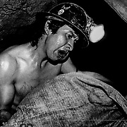 The miners take turns in working on the seam, in pairs; there is no room for more in the tiny dug out of the depths of the earth. Siglo XX  tin mine. Llallagua, Bolivia.