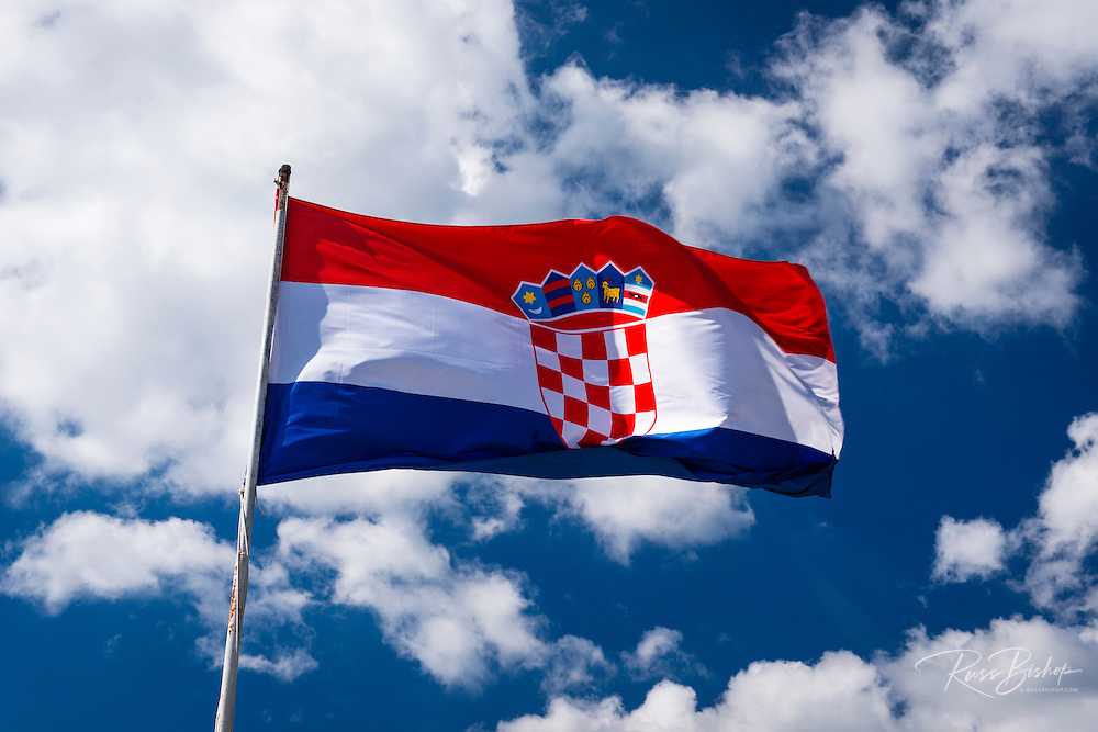 Croatian flag against blue sky and clouds, Ston, Croatia