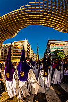 Hooded Penitents (Nazarenos) in the procession of the Brotherhood (Hermandad) San Benito pass the Las Setas (Metropol Parasol), a wooden structure, Holy Week (Semana Santa), Seville, Andalusia, Spain.