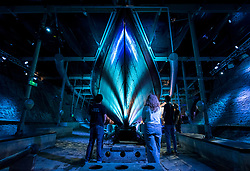 """© Licensed to London News Pictures; 19/08/2021; Bristol, UK. Staff view the illuminated hull of the ship SS Great Britain in dry dock for the """"Iron Island: SS Great Britain Refloated"""" experience. From 23 August to 19 September the dry dock will be transformed into an immersive experience by award-winning multimedia design studio Limbic Cinema, combining projection, lighting and surround sound to transport audiences on a journey through underwater worlds.<br /> Much of the 1,000 square metres of laminated glass overhead will be darkened, providing a unique space for projection-mapped imagery to emerge on the walls and the iron hull. Music and sounds of the ocean will be played, with an original score composed by Joe Acheson (Hidden Orchestra). Performance poet, Saili Katebe, has written a new spoken word piece for this installation, which leads the narrative and which explores themes of invention, discovery, migration and freedom. Events depicted through the storytelling are developed from passenger diaries, providing a real sense of revisiting the ship's long and dramatic history. The SS Great Britain was designed by Isambard Kingdom Brunel and constructed between 1839 and 1843, and was the first iron steamer to cross the Atlantic Ocean. She is now in a dry dock covered with a """"glass sea"""" that helps to maintain the conservation environment that protects the fragile iron hull. Photo credit: Simon Chapman/LNP."""