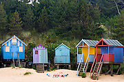 Couple sunbathe outside their beach hut in Wells-Next-The-Sea, Norfolk, United Kingdom