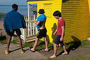 Teenage boys carrying bathing towels walk past a yellow beach hut while enjoying fine summer weather on the seafront promenade at Whitstable, on 18th July 2020, in Whitstable, Kent, England.