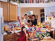 The Caven family in the kitchen of their home in American Canyon, California, with a week's worth of food. Craig Caven, 38, and Regan Ronayne, 42 (holding Ryan, 3), stand behind the kitchen island; in the foreground is Andrea, 5. From the book Hungry Planet: What the World Eats (Model Released)